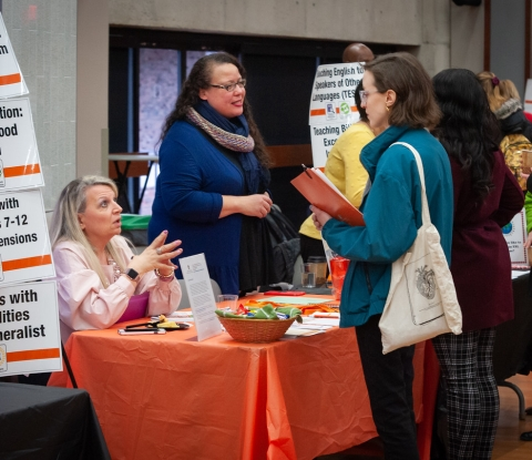 Teachers and student at information table