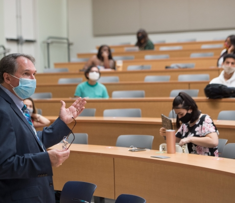 Faculty member in a mask lecturing to students spaced far apart