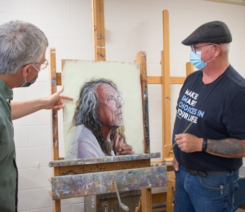 Instructor advises student in front of painting canvas
