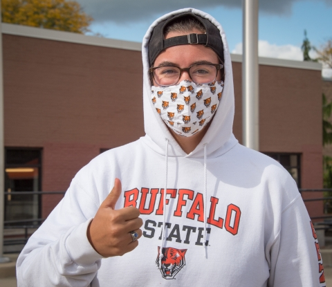 Buffalo State student wearing mask gives thumbs up sign