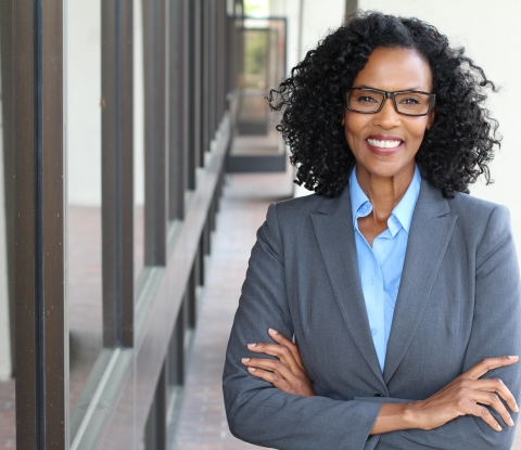 Smiling business woman stands with arms folded