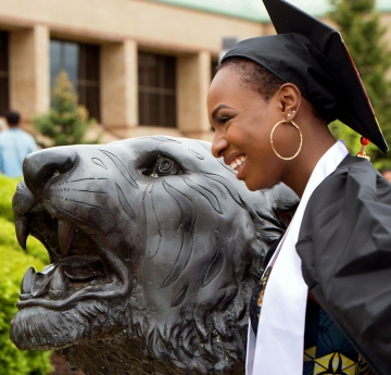 Commencement student with the bengal statue