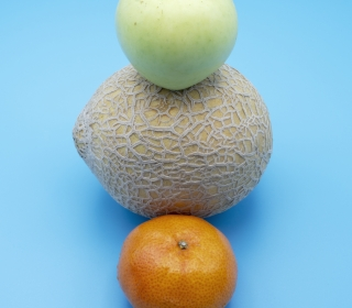 An apple, cantaloupe, and orange artfully stacked