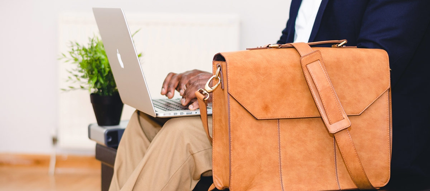 Man sitting with laptop and briefcase