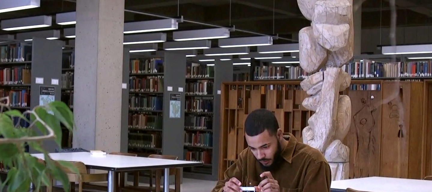 Hector Rosario working on a phone in the library