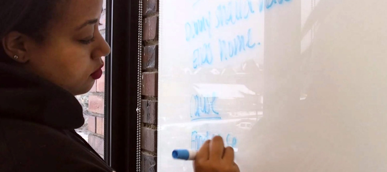 Taylor Seymour writing on a whiteboard