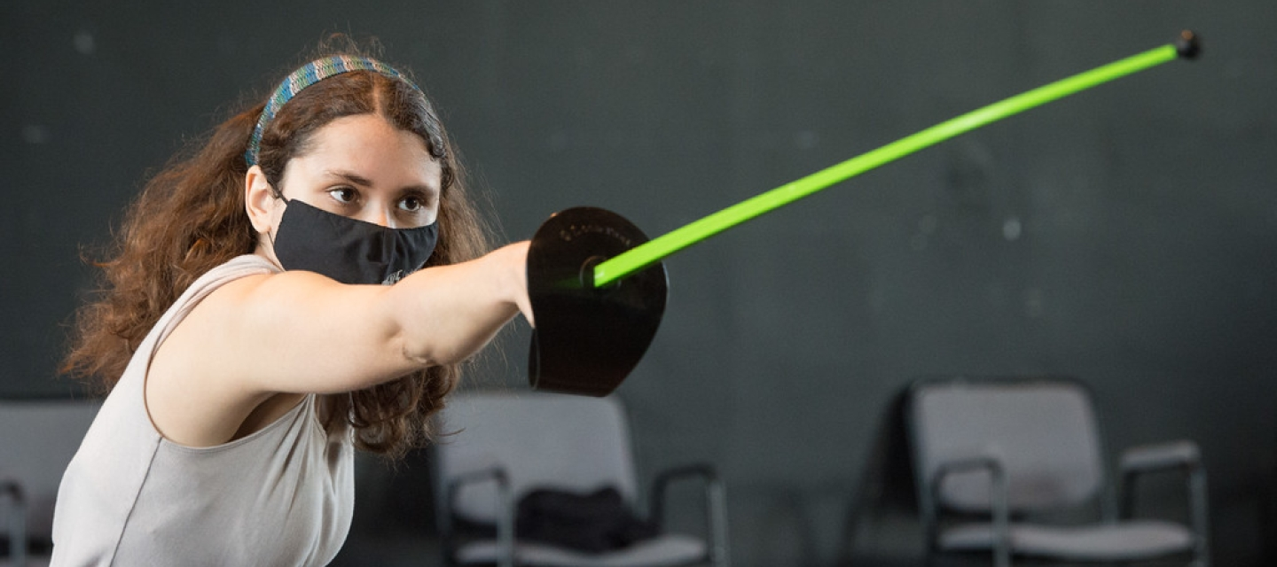 Female theater student holds an outstretched plastic fencing foil