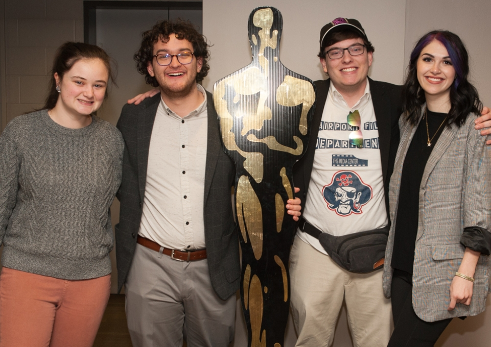 Four students posing with life-size Oscar statue