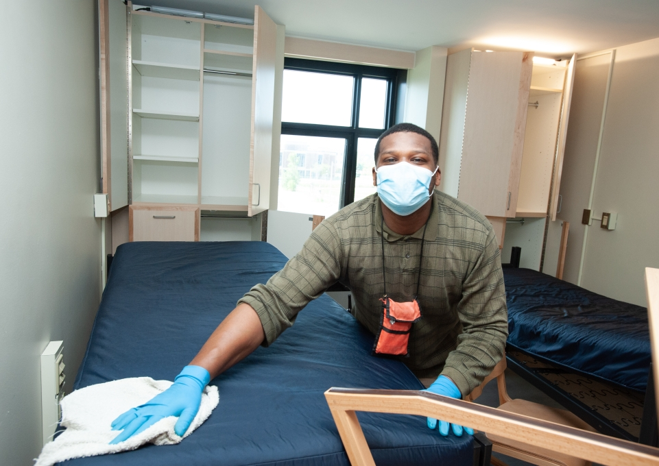 Worker cleaning a residence hall room