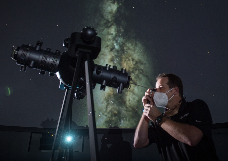 Howard George, Projection Systems Engineer with Seiler Planetarium Division, looking through projection telescope
