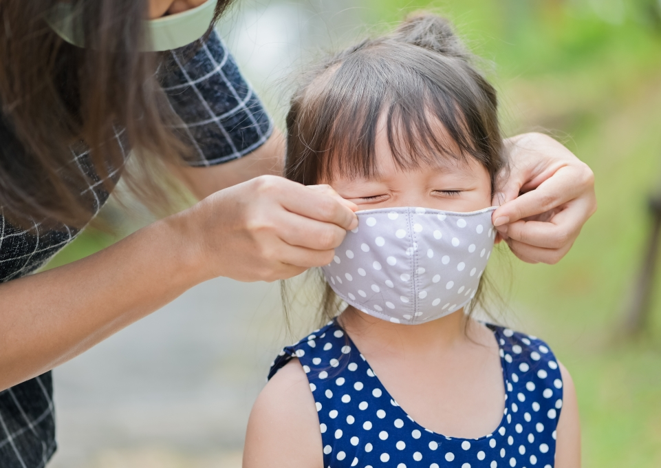Young girl grimacing as adult puts mask on her face
