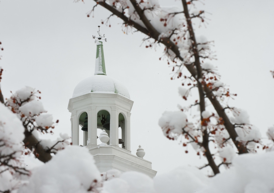 Snow covered Rockwell Hall bell tower surrounded by branches